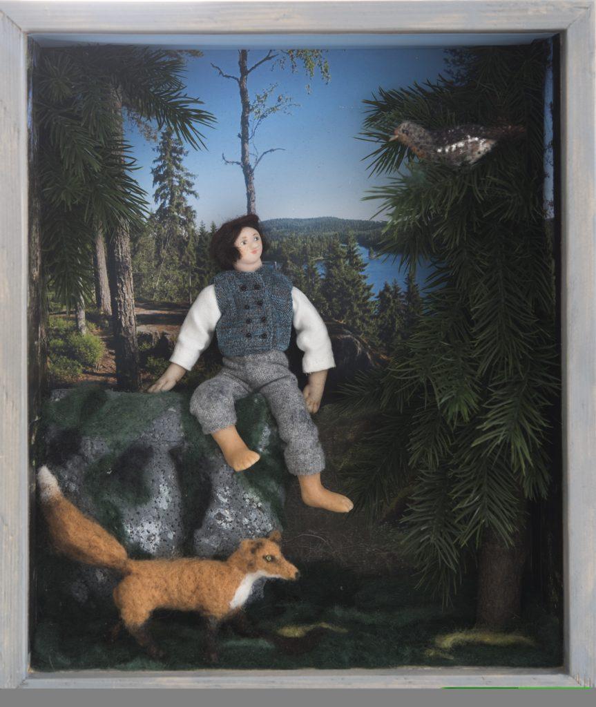 Kuvassa huovutettu pienoismaailma, jossa mies istuu kiven päällä. Kuusessa on lintu ja maassa kettu. Taustalla metsämaisema.