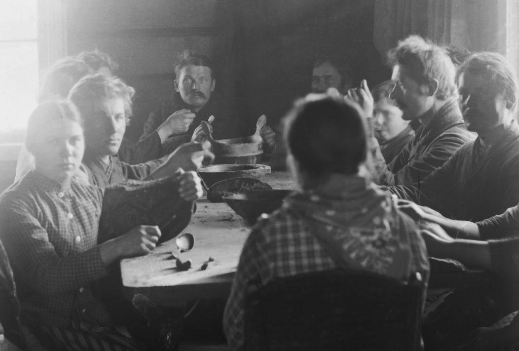 Yli kymmenen ihmistä on kokoontunut syömään pitkän pirtinpöydän ääreen. Pöydällä puisia astioita. Pöydän päässä istuva mies katsoo suoraan kameraan.